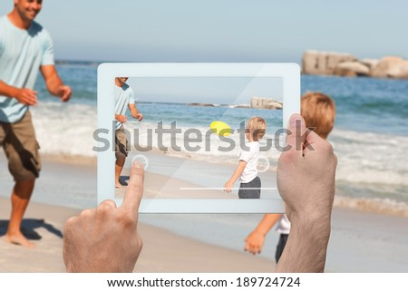 Hand holding tablet pc showing father playing frisbee with son at beach - stock photo