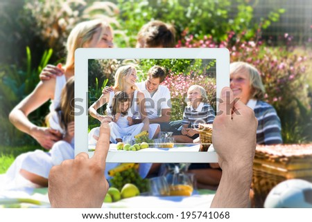 Hand holding tablet pc showing happy family having a picnic - stock photo