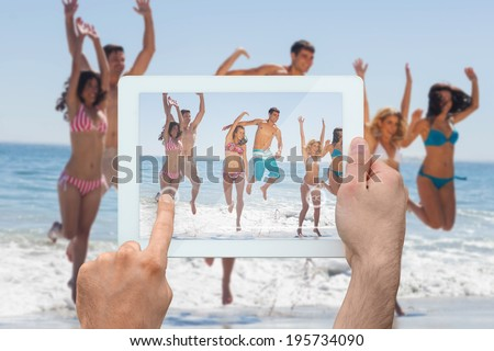 Hand holding tablet pc showing happy friends jumping on the beach - stock photo