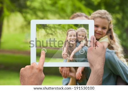Hand holding tablet pc showing mother giving daughter a piggy back - stock photo