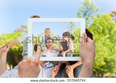 Hand holding tablet pc showing parents giving children a piggyback - stock photo