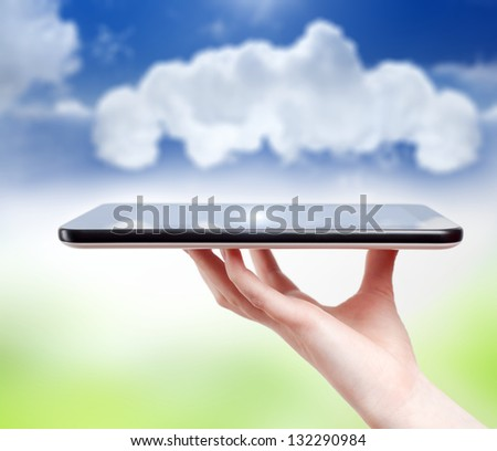 Hand holding tablet PC, smartphone, shallow depth of field. Concept of cloud computing.