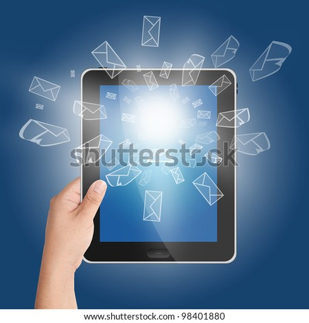 Hand holding tablet PC with 3D mail icon coming from the screen on blue background - stock photo