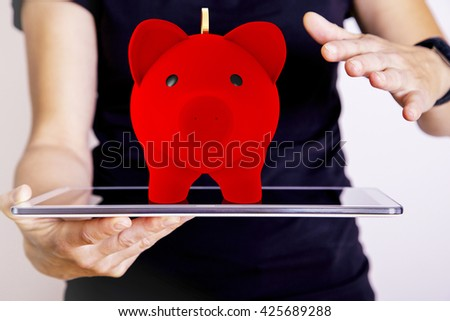Hand holding tablet PC with piggy bank