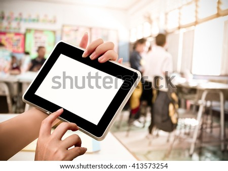 hand holding tablet with blur student in classroom background - stock photo