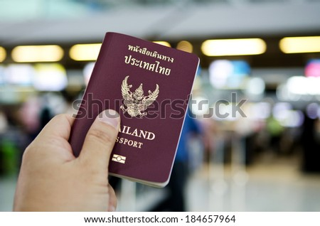 hand holding Thailand passport with gate of airport background - stock photo