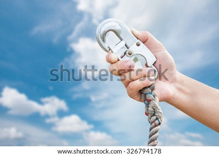 Hand holding the belt lock on sky background .clipping path - stock photo