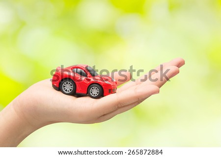 hand holding the model of car on green background. symbol photo for car purchase - stock photo