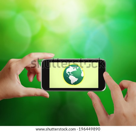 hand holding the phone tablet touch computer gadget with green globe as concept  - stock photo