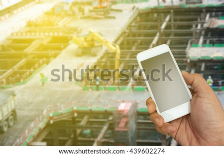 hand holding the smartphone on blurred construction site background with burst light