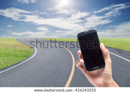 hand holding the smartphone on Roads Curve with green grass blue sky and cloud background - stock photo