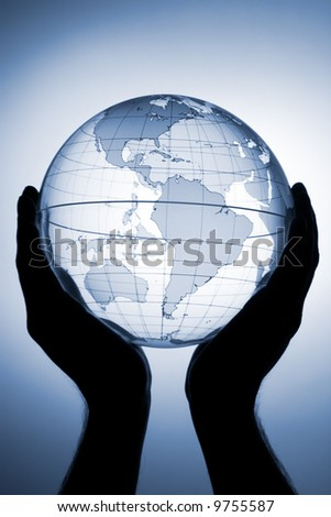 Hand holding translucent globe with blue background - stock photo