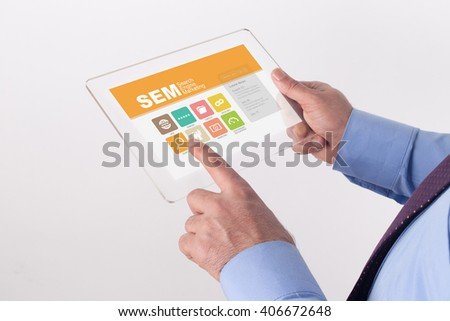 Hand Holding Transparent Tablet PC with SEM Search Engine Marketing screen