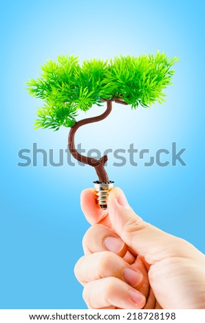 hand holding tree growing on light bulb with light blue sky ,eco concept,eco power - stock photo