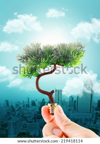 hand holding tree refreshing on light bulb on sky with cloud and cityscape,eco concept,Clear pollution at city with green ideas. - stock photo