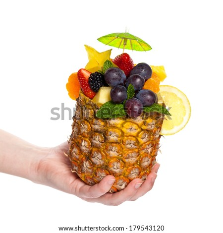 Hand Holding Tropical Fruit Cocktail prepared in pineapple - stock photo
