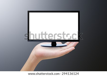 Hand holding tv on dark  background - stock photo