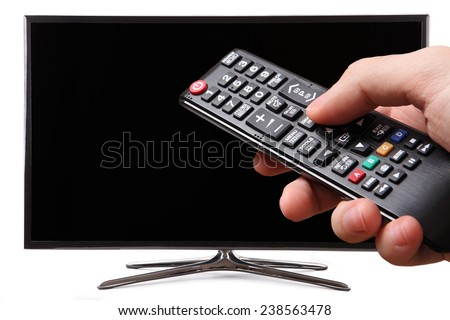 Hand holding TV remote control with a smart tv in the background - stock photo
