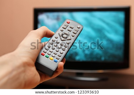 Hand holding TV remote control with a television in the background - stock photo