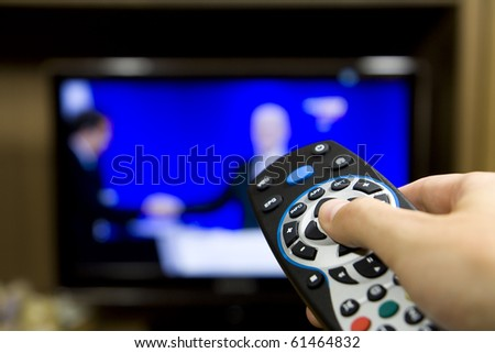 Hand holding TV remote control with a television in the background. Close up.