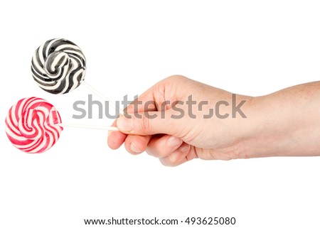Hand holding two spiral lollipops isolated on white background