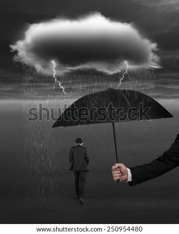 Hand holding umbrella protecting walking businessman from dark cloud of rain and lightning over his head