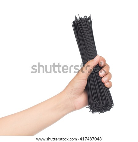 Hand holding uncooked black spaghetti isolated on white background.
