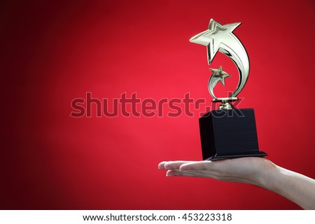 hand holding up a gold star trophy cup as a winner in a competition