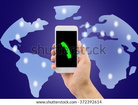 Hand holding up a smart phone in concept the roaming with a world background - stock photo