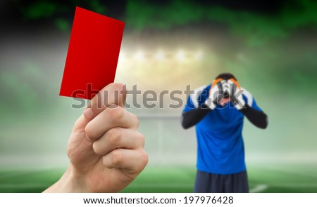 Hand holding up red card against football pitch under spotlights with goalie - stock photo