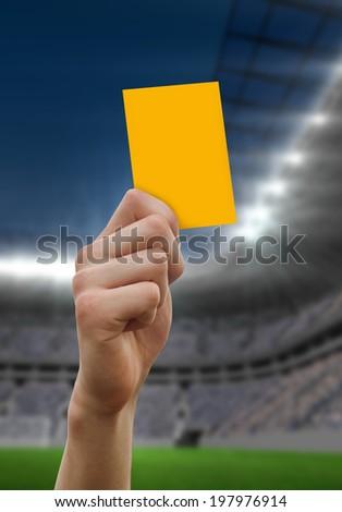 Hand holding up yellow card against football stadium - stock photo