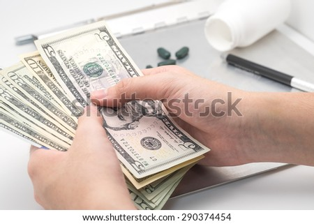 Hand holding US dollar banknotes or bills with medicine for medical background