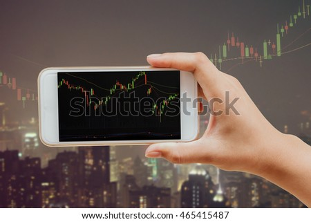 hand holding, using mobile smart phone with stock chart on black screen at the glass window of city view background : Business and technology concept