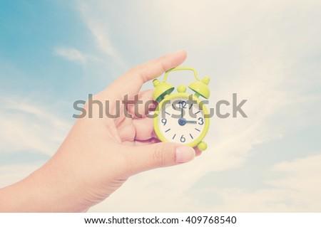 Hand holding vintage alarm clock. - stock photo