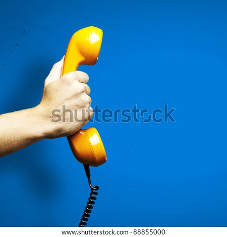 Hand holding vintage telephone receiver isolated over blue background - stock photo