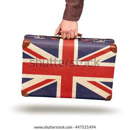 Hand holding vintage Union Jack flag suitcase isolated on white - stock photo
