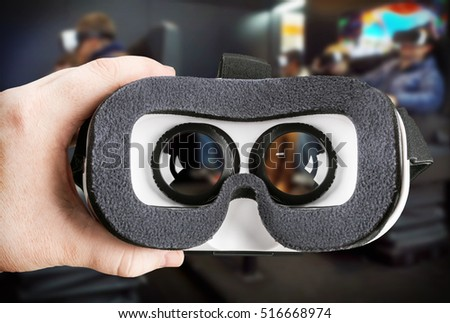 hand holding virtual glasses on the background of the cinema hall