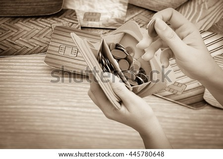 hand holding wallet full of coins with blur credit card background - stock photo