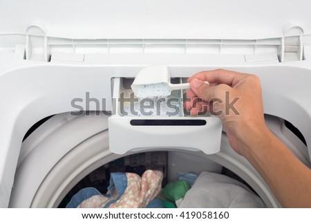 Hand holding washing powder in washing machine. - stock photo