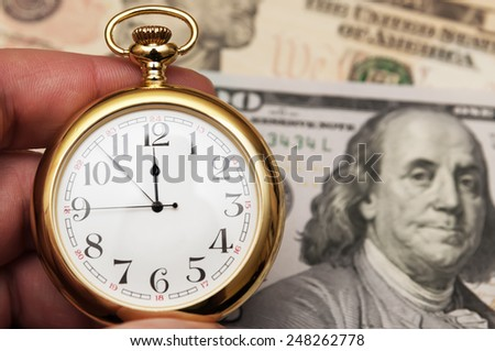 Hand holding watch on dollar banknotes - stock photo