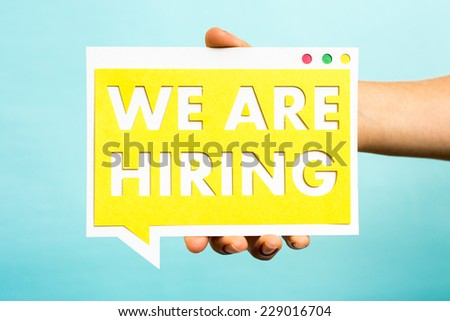 Hand holding we are hiring announcement with cutout letters paper on vibrant yellow speech bubble and all over blue background. Job concept. - stock photo