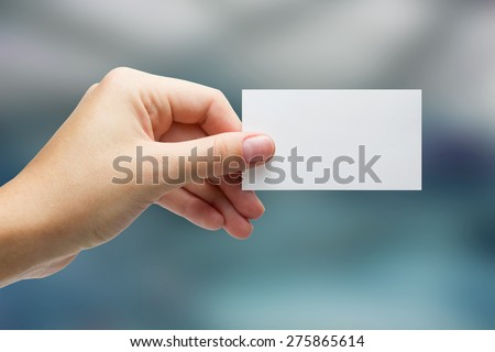 Hand holding white blank business card on blue blurred background. Copy space - stock photo