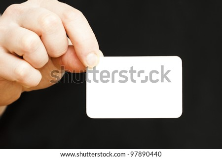 hand holding white business card on black background, See my portfolio for more - stock photo