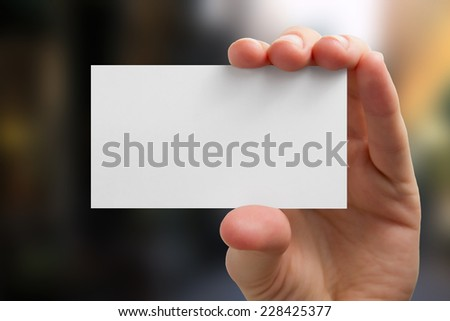 Hand holding white business card on blurred background,