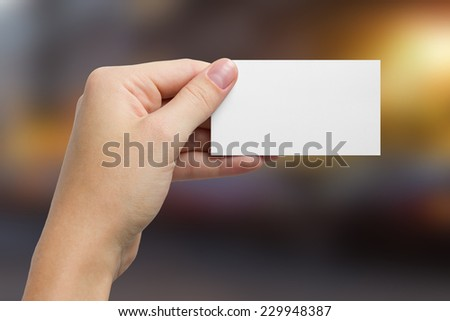 Hand holding white business card on blurred background