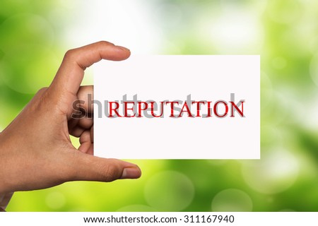 hand holding white card written reputaion over blur background - stock photo