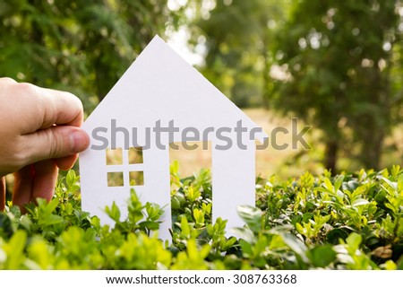 Hand holding white paper house against green background. Real Estate Concept