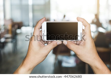 hand holding white  smartphone with blank screen in coffee shop backgroun