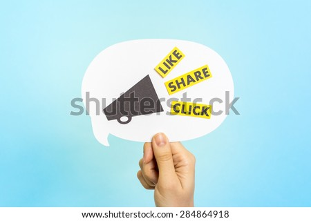"Hand holding white speech bubble with megaphone and the words ""LIKE"" ""SHARE"" ""CLICK"", on blue background. Social media and internet concept. - stock photo"