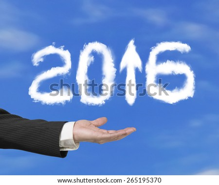 Hand holding white 2016 year arrow up sign shape clouds on blue sky background - stock photo